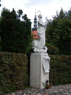 FOTKA - Panna Marie již není v exilu, od r. 1994 je doma, pod Strahovským klášterem; stojí na dva metry vysokém podstavci a nohou zašlapuje saň, která symbolizuje zlo. Je na jednom z nejhezších vyhlídkových míst nad Prahou.