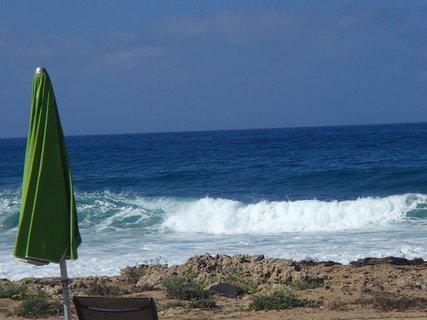 FOTKA - zelený slnečník je sklopený, veľký vietor privial vlny