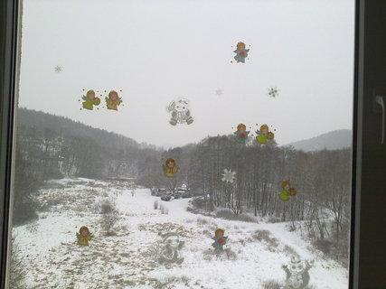 FOTKA - okno s vánočníma nálepkama a za něma zasněžená krajina